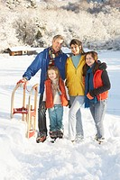 Young Family Standing In Snowy Landscape Holding Sledge