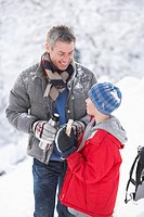 Father And Son Stopping For Hot Drink And Snack On Walk Through Snowy Landscape