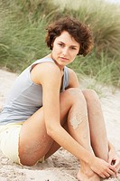 Attractive Young Woman Sitting Amongst Sand Dunes