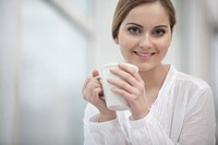 portrait of young woman holding coffee cup