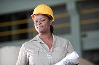 Black worker in hard_hat holding blueprints