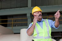 Hispanic worker in reflector_vest and hard_hat talking on cell phone