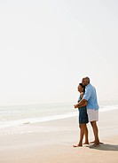 Black couple hugging on beach