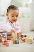 Mixed race baby playing with blocks