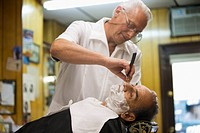 Barber giving customer old_fashioned shave in barbershop