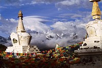 Tibetan prayer flags hanged by big stupas overlooking Kawa Karpo and the Meili mountain range