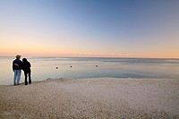 A couple watches the sunset over the Atlantic ocean off Islamorada in the Florida Keys