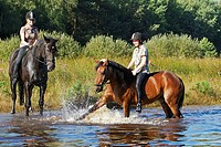 two children on horses in water