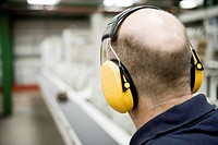 Carpet factory worker wearing sound_proof protective headphones