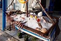 Small ice-filled boat filled with octopus and other seafood in front of a restaurant on the island of Naxos in Greece