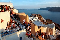 Tourists gathering to watch the sunset in the village of Oia on the island of Santorini in Greece