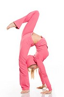 Profile of skillful female wearing pink sportswear doing aerobics over white background