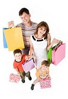 Portrait of happy couple and their two sons with shopping bags looking at camera and smiling