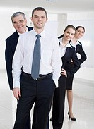 Portrait of successful businessman looking at camera on background of several co_workers
