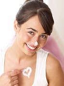 Smiling woman applying creme