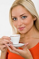 The portrait of young blonde woman with a cup of coffee in her hands