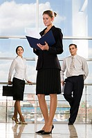 Smiling Caucasian businesswoman reading documents in modern office building and two businesspeople on the background