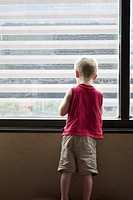 A young boy looking out a high window