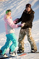 Photo of two snowboarders holding each other by hands while on the snow
