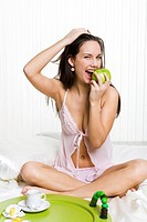 Portrait of healthy woman sitting on bed and eating fresh green apple