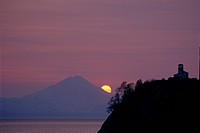 View across Cook Inlet of Mt. Redoubt and a lighthouse at sunset,/nSouthcentral Alaska, Summer