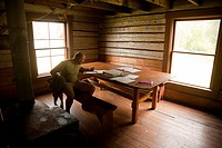 A visitor writes in a log inside the historical Slaven´s Roadhouse along the the Yukon River, Yukon_Charley Rivers National Preserve, Interior Alaska,...