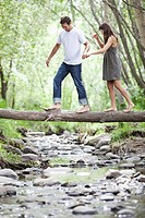 Couple walking across stream on log