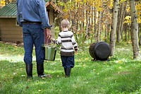 Father and son carrying compost