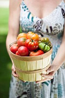 Woman holding basket of tomatoes