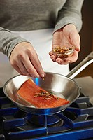 Woman seasoning salmon as it is cooking