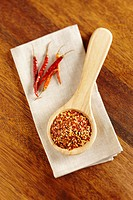 Wooden spoon containing hot red pepper flakes