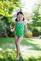 Girl playing in sprinkler (thumbnail)