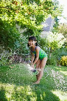 Girl playing in sprinkler