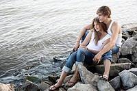 Young couple sitting on rocks by the water