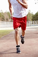 Photo of male in sportswear running down stadium track
