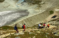Hikers on a narrow path descending from the Moiry Hut, Pennine Alps, Valais, Switzerland, Europe