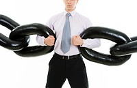 Powerful businessman holding sections of huge chain over white background