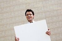 Image of successful male with blank paper looking at camera and smiling