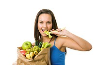 Portrait of pretty girl with paper sackfull of fruits and vegetables while eating celery and looking at camera with smile