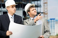 Portrait of successful workers holding a project and discussing a building place