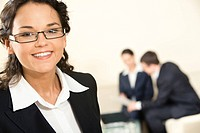 Close_up of happy business lady on the background of working business team
