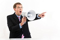 Portrait of unhappy man in suit speaking through megaphone and pointing aside