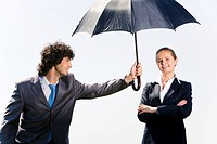 Conceptual image of businessman holding a black umbrella over his colleague