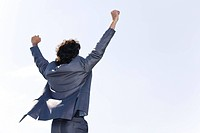 Back of successful businessman in suit raising his hands
