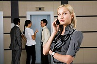Photo of female employee speaking on the phone with interacting people at background