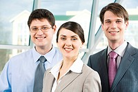 Portrait of smiling business people looking at camera together on the background of window