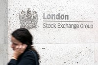 Woman in front of the logo of the London Stock Exchange Group, in London, England, United Kingdom, Europe