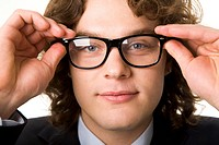 Close_up of face of clever man looking at camera through eyeglasses