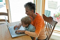 Grandmother and grandson using laptop