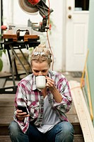 Woman sitting on steps with smartphone drinking hot drink